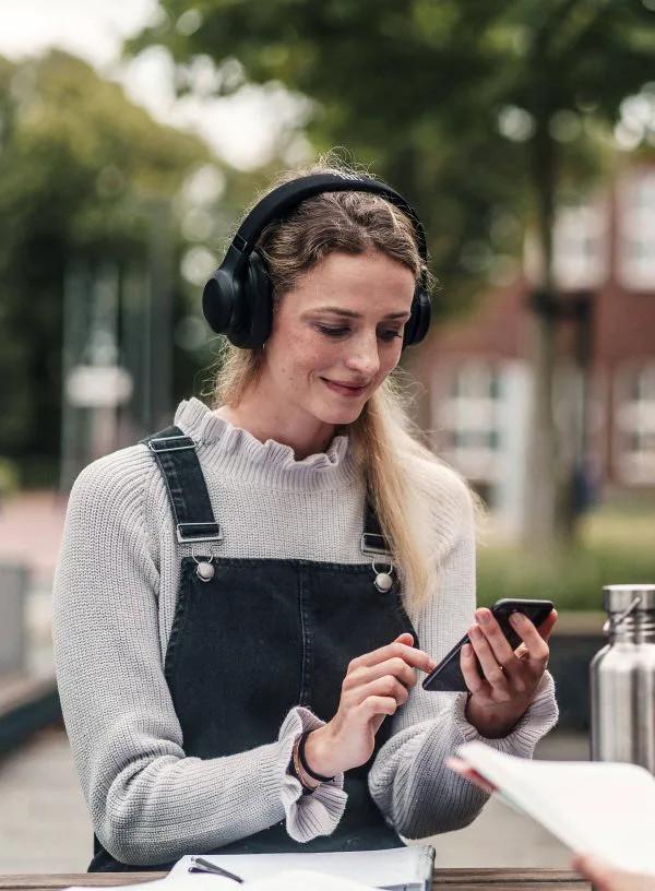 Studierende benuttz ihr Smartphone und informiert sich über die Audio-Uni - das Projekt mit der Hoschule ohne Hemmungen